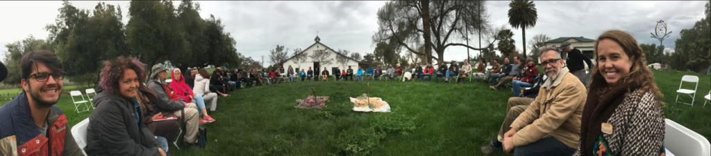 Panoramic photo of people sitting in chairs in a large circle on a green lawn, smiling at the camera. There is a large barn in the background, as well as trees.